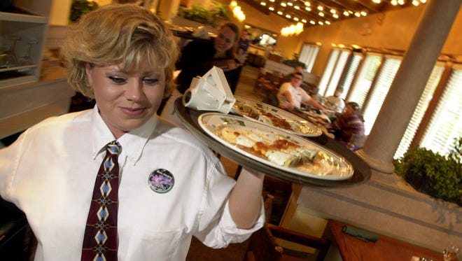 A waitress delivers orders at The Olive Garden. The restaurant is adding catering delivery.