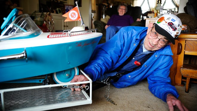 Clarence Zeigler, 76 of Jackson Township, shows the 1966 Murray pedal-car boat he restored, which sits atop a trailer he made, in his Jackson Township living room.