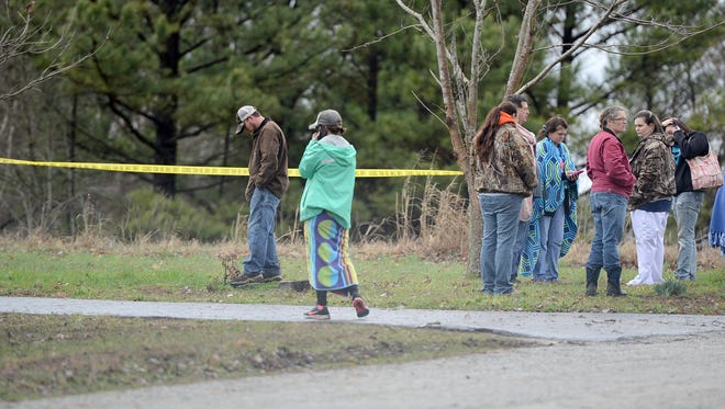Friends and family gather outside of the scene of a fatal house fire in Henderson County, Tuesday morning.