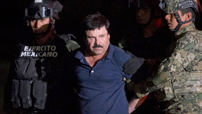 """In this Jan. 8, 2016 file photo, Mexican drug lord Joaquin """"El Chapo"""" Guzman is escorted by army soldiers  to a waiting helicopter, at a federal hangar in Mexico City, after he was recaptured from breaking out of a maximum security prison in Mexico."""