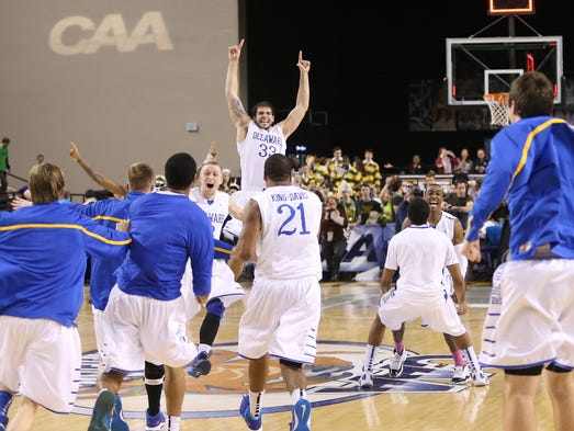 The Blue Hens, including Carl Baptiste (33) celebrate their 75-74 win against William and Mary after time expired in the CAA Championship game Monday, March 10, 2014 at the Baltimore Arena.