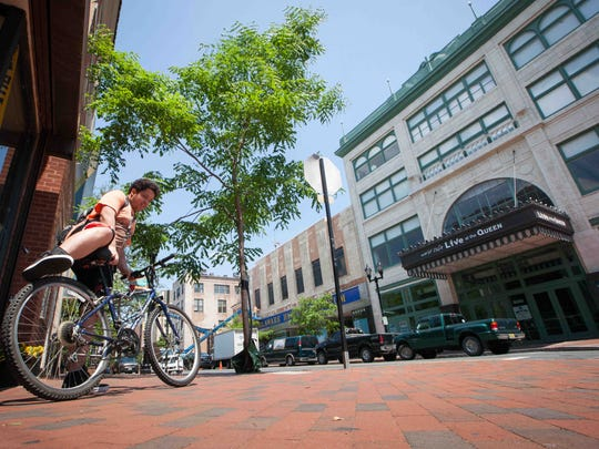 A rider hops on his bike along North Market in downtown Wilmington on May 22.