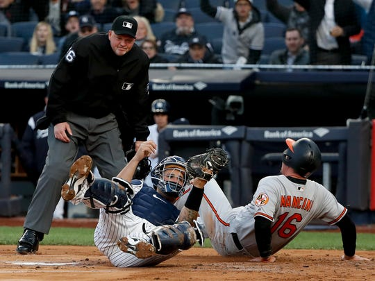 New York Yankees catcher Gary Sanchez, front left, holds onto the ball after tagging out Baltimore Orioles' Trey Mancini (16) during the first inning of a baseball game, Thursday, April 5, 2018, in New York. Mancini was initially ruled safe on the play but the call was overturned after an instant replay review. (AP Photo/Julie Jacobson)