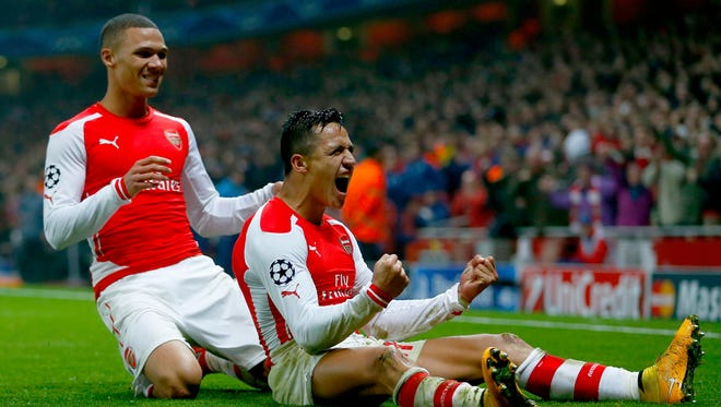 Arsenal's Alexis Sanchez celebrates with teammate Kieran Gibbs (L) after scoring a goal against Borussia Dortmund during their Champions League group D soccer match.