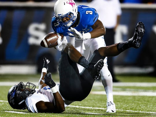 University of Memphis receiver Anthony Miller (top) fumbles a catch after University of Tulsa defender Diamon Cannon (bottom) pulls the ball loose during first quarter action at the Liberty Bowl Memorial Stadium. Miller recovered the loose ball to help the Tigers score on the drive.