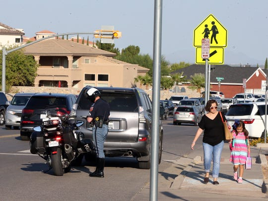 An El Paso police officer issues a traffic citation as parents cross Bear Ridge Drive to drop off their children at Tippin Elementary School on Tuesday morning.