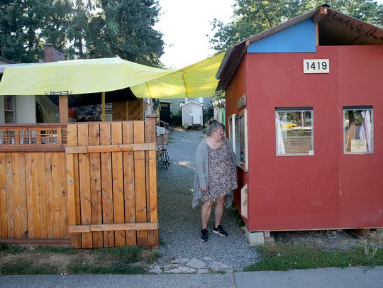 Kelly Lyons, a resident of the Seattle's Tiny Home Village, visits with the security booth attendant at the entrance of the village.