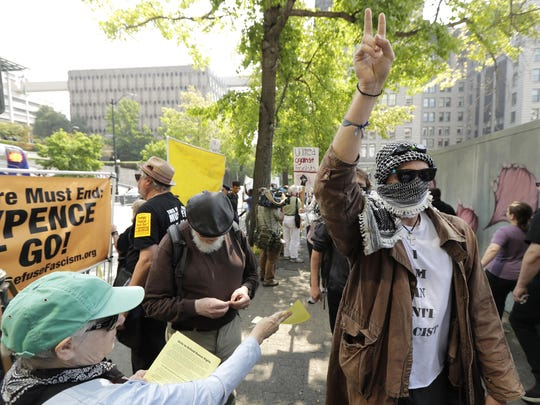 A protester holds up a peace sign while marching on the side of the street of anti-fascist groups counter-protesting as members of Patriot Prayer and other groups supporting gun rights demonstrate across the street.