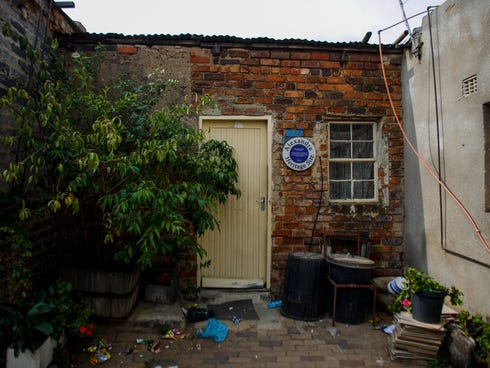 A plaque hangs near the front door of the first home of former South African President Nelson Mandela in Alexandra, Johannesburg, on Saturday.