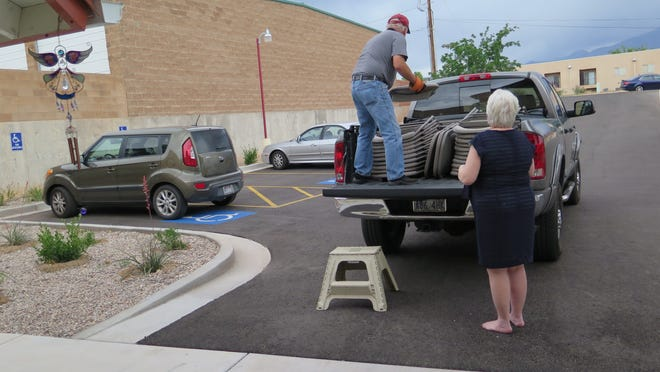 Sue Kimball helps Mike Cummins gather chairs after the open house and ribbon cutting of the now-finished Erin's Home in Washington City.