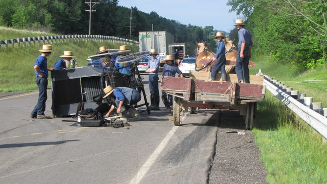 Members of the Amish community work to right a horse and buggy that was struck along Ohio 42. Fannie Hostetler, 70, suffered serious injuries Tuesday and was taken to Cleveland MetroHealth hospital.