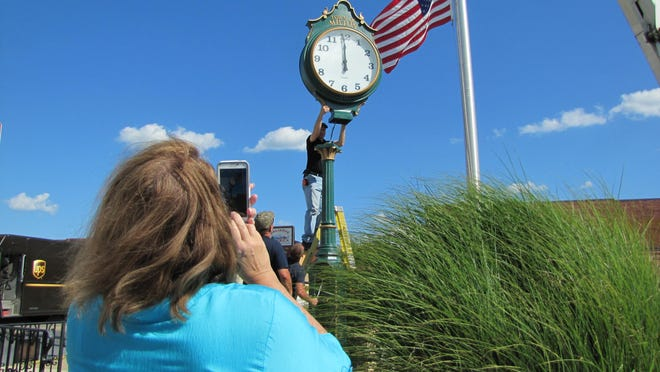 Bette McGrath of Milton takes a photo as the new clock at the corner of Union and Magnolia streets is installed Wednesday, July 22.