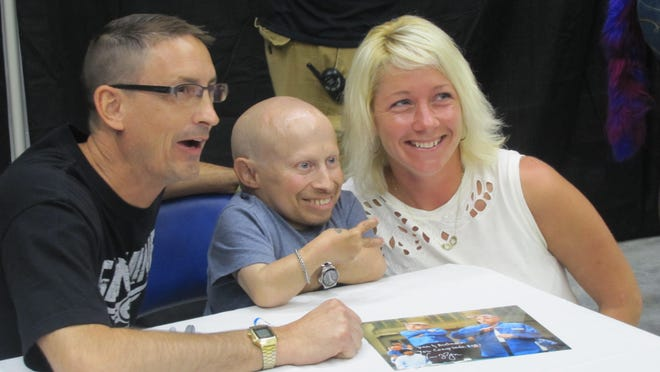 """Bath residents Dan Brown, left, and Autumn Spears, right, surround actor Verne Troyer, who has appeared in """"Austin Powers"""" and """"Harry Potter"""" films, during an autograph and photograph session Saturday at Twin Tiers Comic-Con at First Arena, Elmira."""