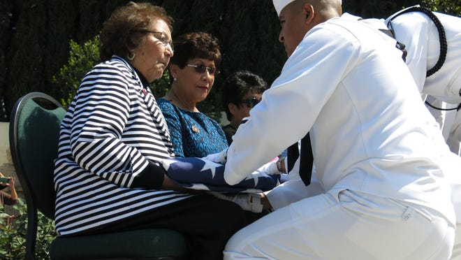 A sailor presented the American flag to Helen Fabela Chavez during an April 2015 graveside ceremony marking the 22nd anniversary of the passing of her husband, farm worker union organizer Cesar Chavez.