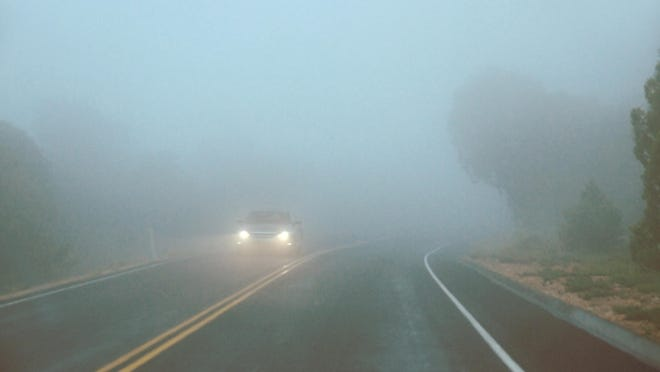 Car driving in a fog with headlights switched on.