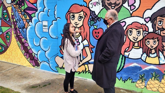 Alexandria Ramirez, left, who started the ball rolling on the Vinewood Park project, explains the features of the mural to Mayor Nick Gradisar.