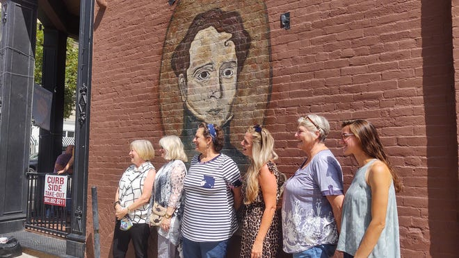 Members of Sherman Main Street pose for a photo around a new mural of Sidney Sherman outside Old Iron Post  Friday morning.