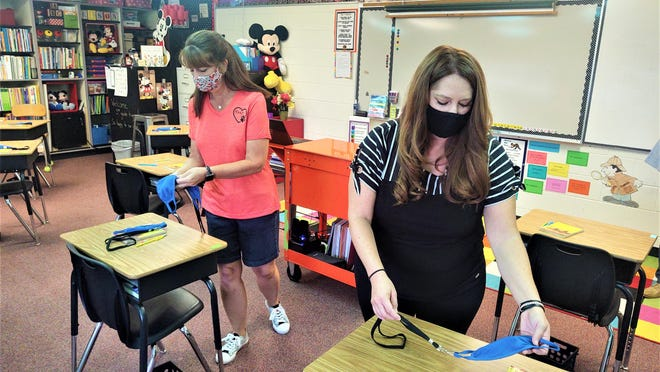 Haaff Elementary School Principal Betsy DeCesaro, right, and fifth grade teacher Shari Elson, place facemasks on desks in preparation for the start of school Monday.