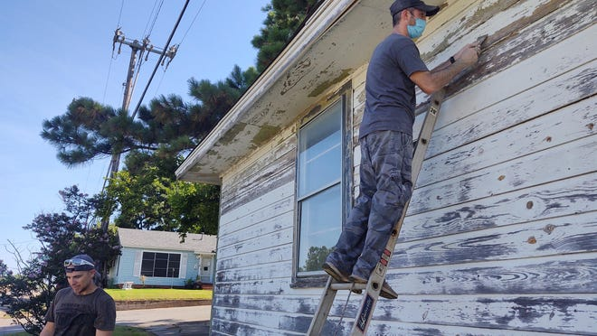 Volunteers work to clean up a house in Denison as a part of the city's new neighborhood revitalization program Friday.
