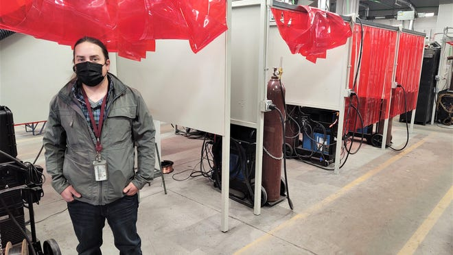 PCC welding program manager Catlin Davis stands in front of new welding stations added as part of the expansion.