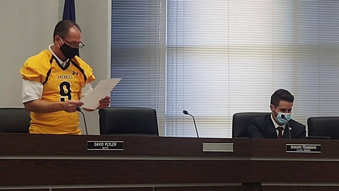 Sherman Mayor David Plyler sports Denison Yellow Jacket colors during a city council meeting Monday. This comes following a lost bet between Plyler and Denison Mayor Janet Gott regarding the outcome of the 2020 Battle of the Ax game.