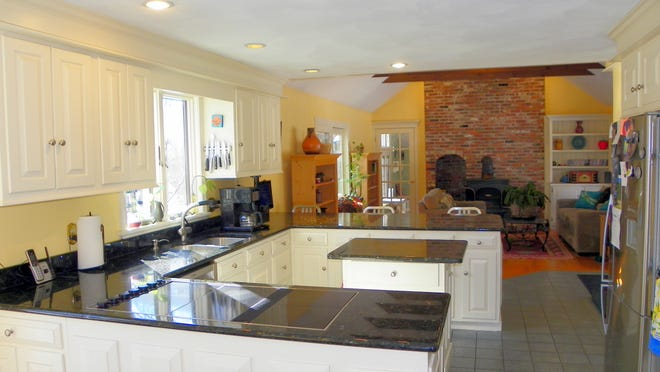 The U-shaped kitchen has stainless steel appliances and granite countertops, and is open to the family room.