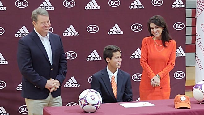 Tristan DeLoach signs to play soccer at Clemson during a ceremony Wednesday at Benedictine, where he is a senior. Also pictured are his parents John and Robin DeLoach.
