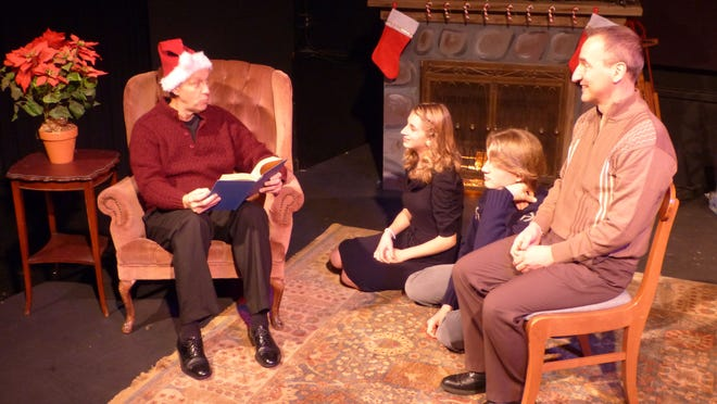 """Robert Boles dons his Santa cap to read a Chistmas story to Michaela Kraft, Isaiah Spetz and James Valcq, from left, in the Stage Door Theater Company production of """"Yuletide Tales"""" at TAP."""