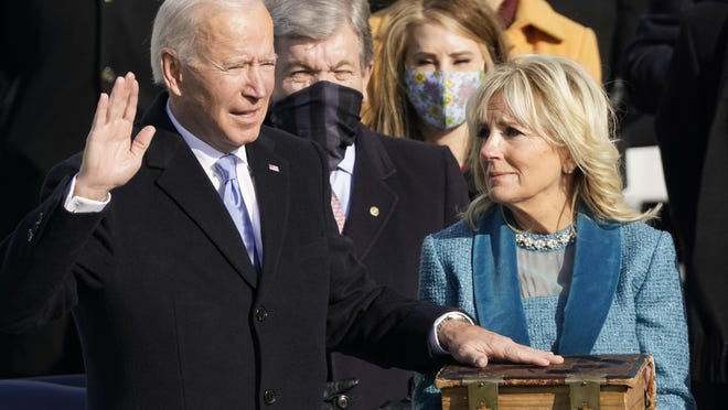 Joe Biden is sworn in Wednesday at the U.S. Capitol in Washington as the 46th president of the United States by Chief Justice John Roberts as Jill Biden holds the Biden family Bible during the 59th presidential inauguration.