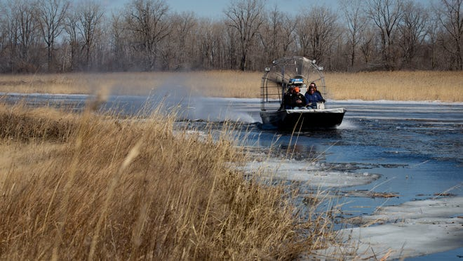 Contractors get a tour on an airboat Wednesday at Krispin Drain on Harsens Island. The Environmental Protection Agency is working on a restoration project to dredge the drain to restore flow, reshape the banks and plant native species.