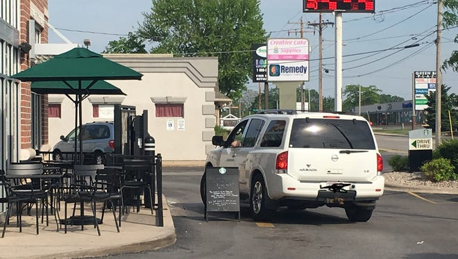 A drive-thru customer attempted to drive around a sandwich board sign to place an order at Starbucks on Military Avenue on the afternoon of May 29. The sign notified customers the store was closed for racial bias training.