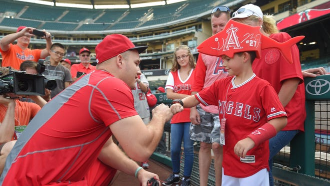 Mike Trout (left) bumps fists with Millville's Thomas Walkup before the Los Angeles Angels hosted Toronto on Friday. Walkup, who recently had a rare eye procedure performed in California, was Trout's special guest at the game.