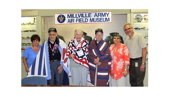 Three World War II veterans were presented Quilts of Valor in honor of their service to the country at a ceremony held on July 12 at the Millville Army Air Field Museum. (From left) Lisa Jester, executive director, MAAFM; World War II veterans Owen Garrison of Bridgeton, Walter Kocielski of Millville and Tim Kiniry of Vineland; Crystal Smith, co-chair of South Jersey Quilts of Valor; and Bob Trivellini, vice president, MAAFM. Each quilt was handmade and signed by area quilters dedicated to honoring America's soldiers and veterans.
