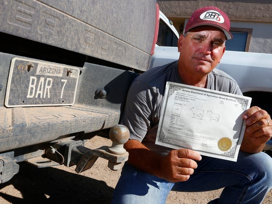 Rancher David Stambaugh holds his cattle brand certificate as he awaits an Arizona Supreme Court decision on whether the state can allow an identical cattle brand to be used by two ranchers Thursday, Aug 3, 2017, in Eloy, Ariz. Stambaugh has owned the Bar 7 brand since he was 10 years old, but the state Agriculture Department allowed a California cattle company to use the same brand.