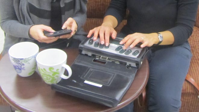A sighted person sends a text message to her deaf-blind friend who receives the message on her refreshable braille display.