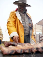 Henry Crawford cooks bacon and ribs in the cold rain during the Christmas at Old Fort Concho event on Saturday.