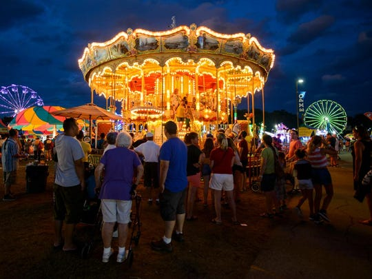 Parents wait for their children as they ride the merry go round during the Champlain Valley Fair on Wednesday evening August 29, 2018.