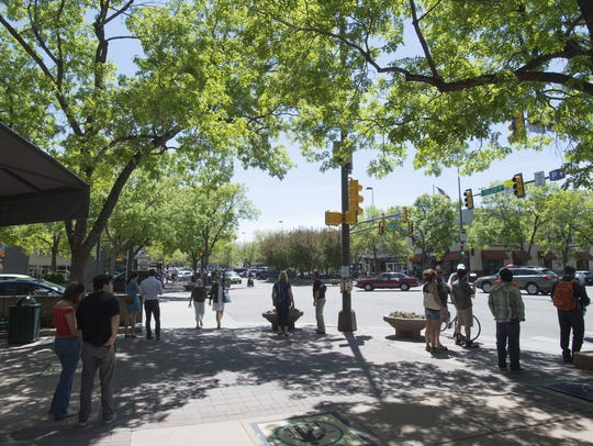 People walk along College Avenue in Old Town on Saturday,