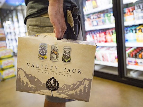 Dom Gambone selects a 12-pack of beer from Odell Brewing Company at Bullfrog Wine and Spirits on N. College Avenue on Thursday, July 27, 2017.