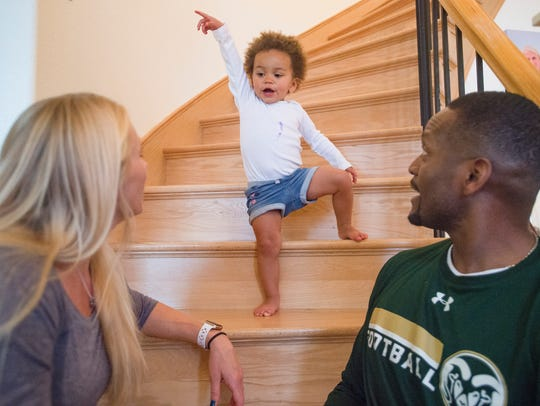 Remy Whitted, the 20-month-old daughter of CSU receivers coach Alvis Whitted and his wife, Tracy, plays with her parents Monday at their Fort Collins home.