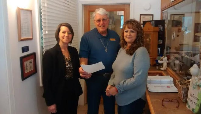 Pictured, from left; are Diane Medcalf and Buddy Moore from Ruidoso Alano Club accepting a donation from Nest Operations Director Susanne Francis.