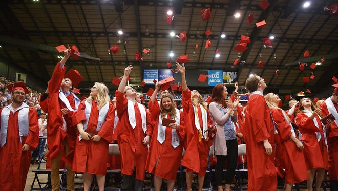 Lincoln High School students throw their hats in the air at the end of graduation, Sunday, June 3, at the Sioux Falls Arena.