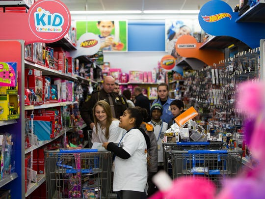 The aisles at Wal-Mart fill with children and officers from area law enforcement agencies during the Shop With a Cop event Saturday morning.