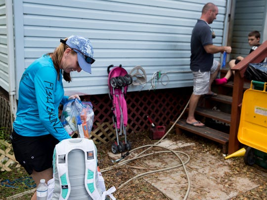 Denise Wright, left, sorts through medical supplies while David Brewer, right, bandages the heel of Christian Keefe, 12, Tuesday, September 19, 2017 in Copeland, Fla. Keefe's foot had become infected after a suspected insect bite turned red after wading in flood waters and caked mud this past week as the small rural community tries to recover from Hurricane Irma.