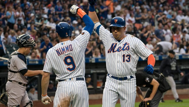 New York Mets center fielder Brandon Nimmo (9) congratulates second baseman Asdrubal Cabrera (13) after hitting a two run home run during the first inning against the New York Yankees at Citi Field.