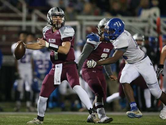 Alcoa quarterback Walker Russell (1) looks to pass