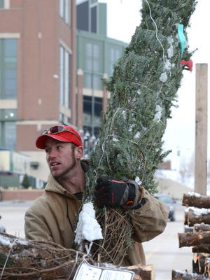 Chris Duffy, of Whispering Pines Tree Farm, Oconto, helps unload Christmas trees, as area Christmas tree growers drop off nearly 225 trees for the Trees for Troops program, at the Lambeau Field parking lot, Tuesday, December 2, 2014.