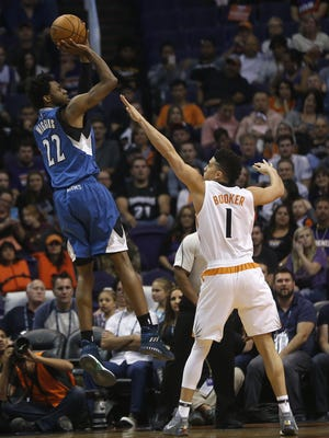 Suns' Devin Booker (1) defends Timberwolves' Andrew Wiggins (22) at Talking Stick Resort Arena on November 25, 2016 in Phoenix, Ariz.