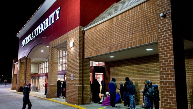 Shoppers wait in temperatures in the mid teens at the Sports authority store November 28, 2014 in Greenfield, Wisconsin.