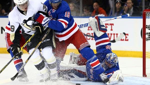 Rangers goalie Henrik Lundqvist (30) makes a save in front of Rangers defenseman Marc Staal (18) and Pittsburgh Penguins left wing David Perron (39) during the first period of game one of the first round of the the 2015 Stanley Cup Playoffs at Madison Square Garden.